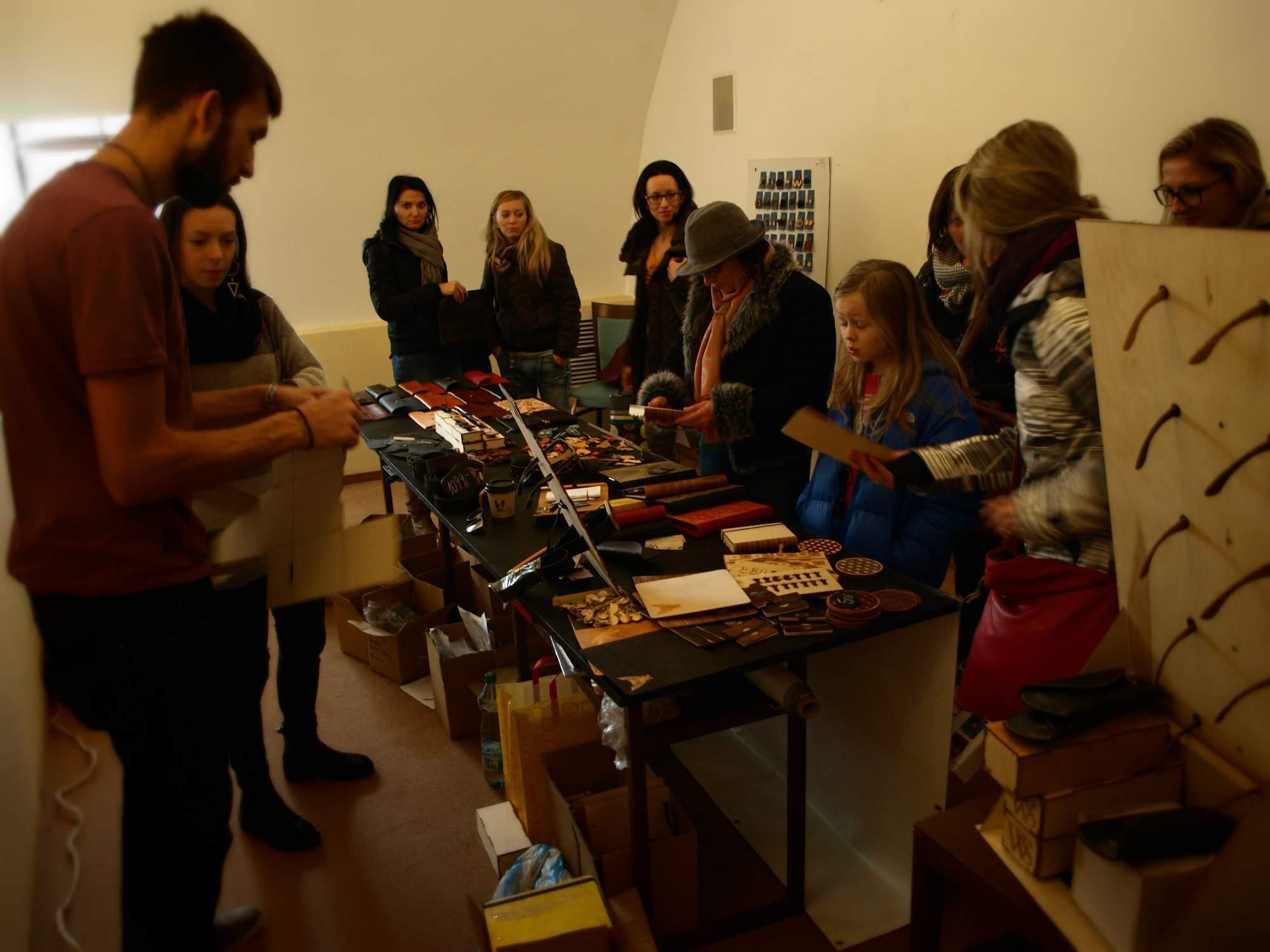 Designéři vyrábějící ze dřeva a kůže ukazují zvědavcům svoji tvorbu. Foto: Bečáková Klára