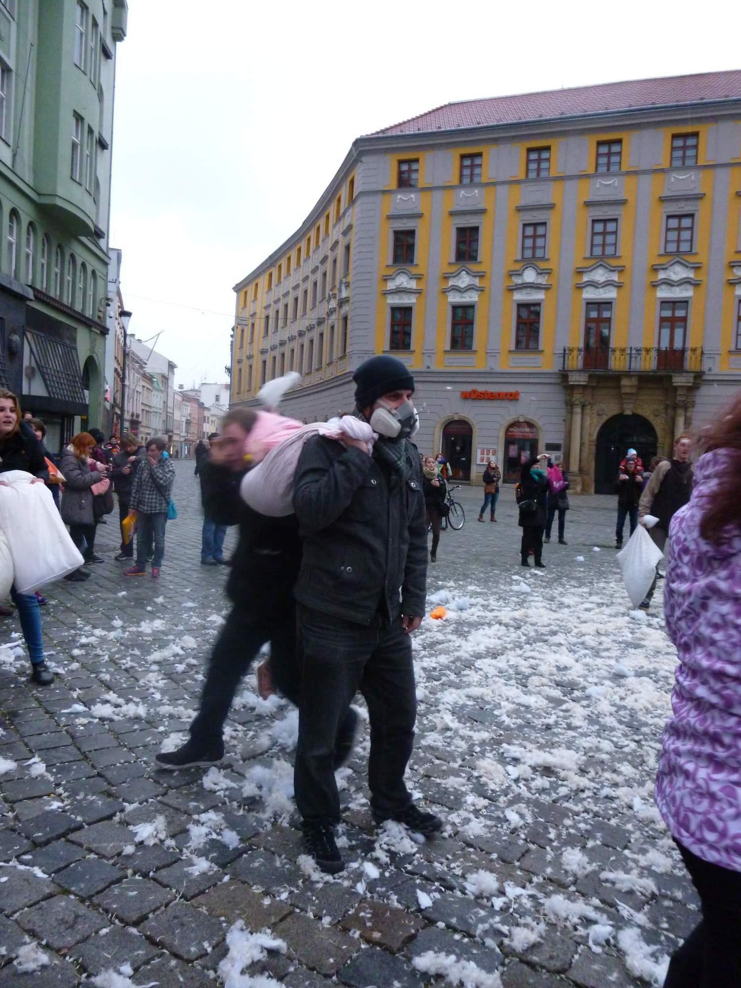 Někteří se poletujícímu peří bránili maskami. Foto: Klára Slavíčková
