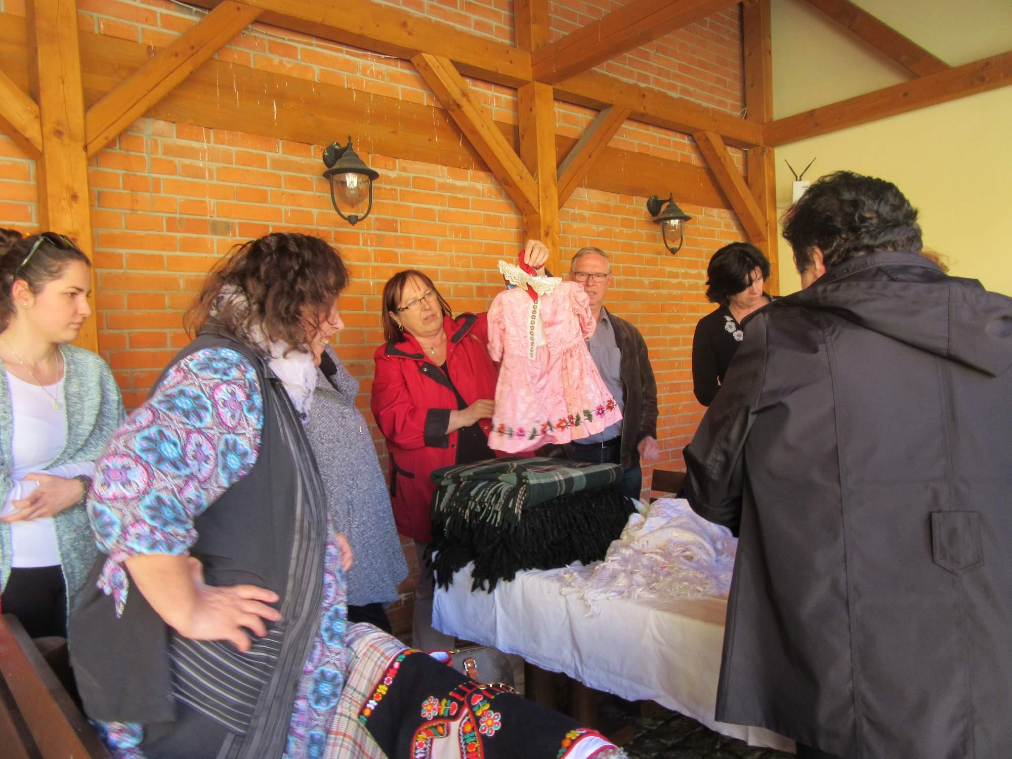 Prodávající seznamuje příchozí s dětským krojem. Foto: Magdaléna Kunrtová