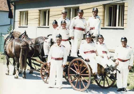 hasiči  - stará garda - stará garda hasičů: nahoře stojící Vacek, Benda a Vavrejn, uprostřed kočí Loukota, vedle Batěk, dále sedící Tomrdle - Vápeníček, hostinský Fremr a Rajtmajer, před kočárem stojí lakýrník Jan Mošna
